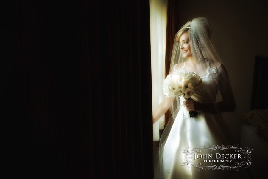 Bridget looks out the window of her hotel room as guests arrive for her wedding at Lake Natoma Inn in Folsom, CA.